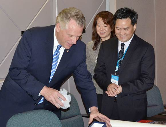 Mr. Terry McAuliffe is giving a gift to Mr. Frank Cao